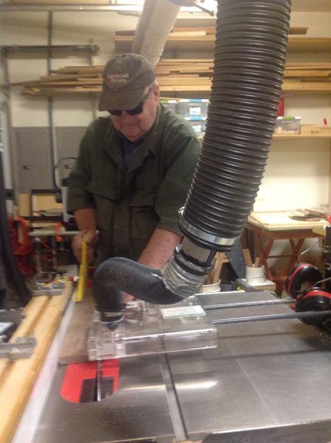 man waring sun glasses ripping a board on a table saw